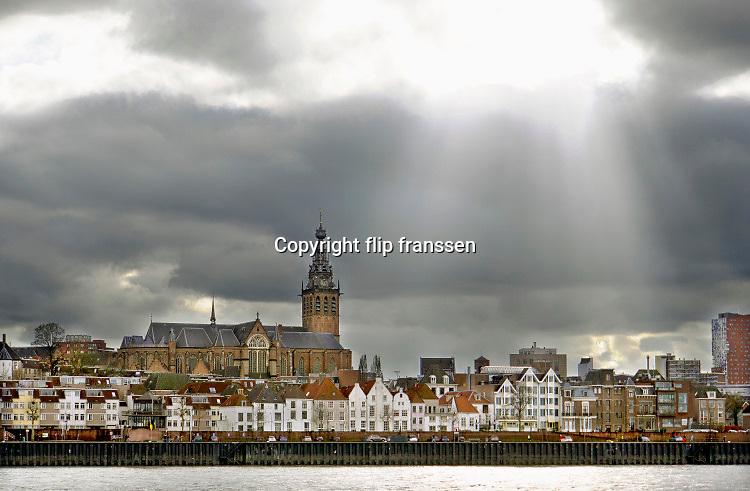 Nederland, Nijmegen, 3-2-2019 Gezicht op Nijmegen en de Waal met de waalkade, benedenstad en skyline van Nijmegen . Zonlicht valt in stralen door een opening in het wolkendek . Vanaf het lentereiland, eiland Lent, veurlent uitzicht op de stevenskerk en binnenstad, stadscentrumFoto: Flip Franssen