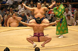 Sumo wrestlers face each other in the ring before bout commences in Tokyo