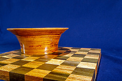 Hand turned wooden oak bowl on wooden checkerboard and dark blue background