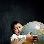 Young boy in classroom holding globe looking at camera.