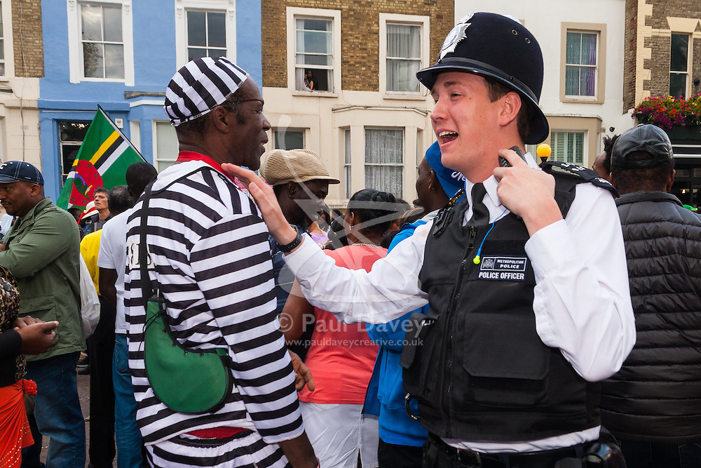 """London, August 24th 2014. A police officer and an """"escaped convict"""" share a joke as thousands of Londoners of all races and cultures attend Notting Hill Carnival's """"Family friendly"""" day ahead of the main carnival on August Bank Holiday Monday."""