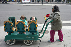 A nanny pushes a truck of toddlers on a Washington street. From a series of travel photos in the United States. Photo date: Thursday, March 29, 2018. Photo credit should read: Richard Gray/EMPICS