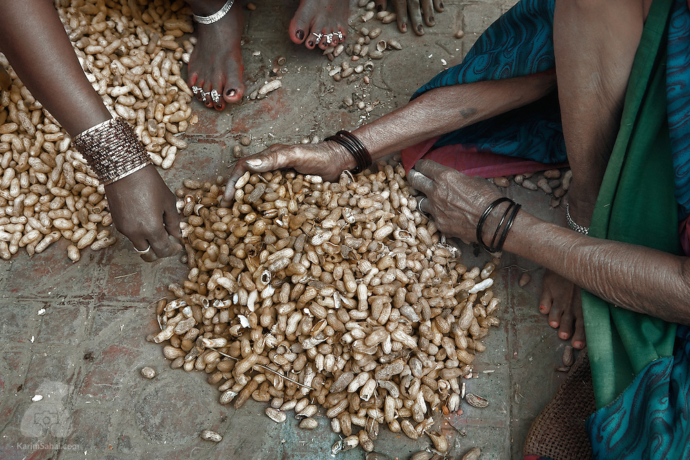 A woman and her grand daughter sift through a pile of peanuts before heading to a nearby market.