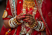 A young girl wearing a traditional bridal outfit at the Desert Festival on 29th January 2018  in Jaisalmer, Rajasthan, India. It is an annual event that take place in February month in the beautiful city Jaisalmer. The bridal dowry is a rich aray of silver and gold jewelry and the hands and arms are adorned with henna patterns.