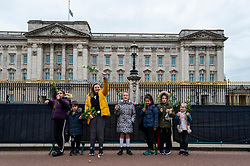 © Licensed to London News Pictures. 10/04/2021. LONDON, UK. Young well wishers from Putney arrive with flowers outside Buckingham Palace after the death of Prince Philip, aged 99, was announced the previous day. [** parental permission obtained **]  Photo credit: Stephen Chung/LNP