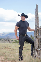 cowboy by a rustic fence looking at the mountain range