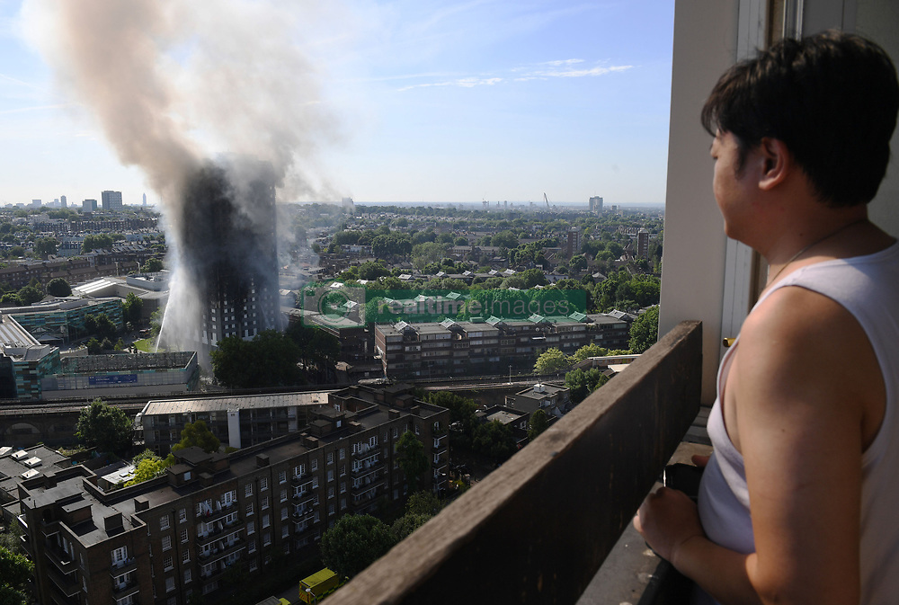 A resident looks on as smoke billows from a fire that has engulfed the 24-storey Grenfell Tower in west London.
