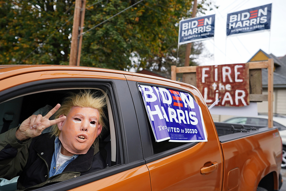 """A participant wears a Donald Trump mask as they look out of their truck as United Steelworkers Local 2599 hosted a """"Ridin' 4 Biden Ticket Caravan"""" on Oct. 25, 2020, in Bethlehem, Northampton County, Pennsylvania. Northampton County is a crucial region for Presidential candidates looking to win Pennsylvania as the county went for Obama in 2012 and then for Trump in 2016. (Photo by Matt Smith)"""