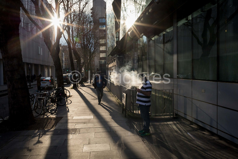 A vaper exhales a cloud of smoke in bright winter sunlight, on a central London street, on 6th February 2018, in London, England.