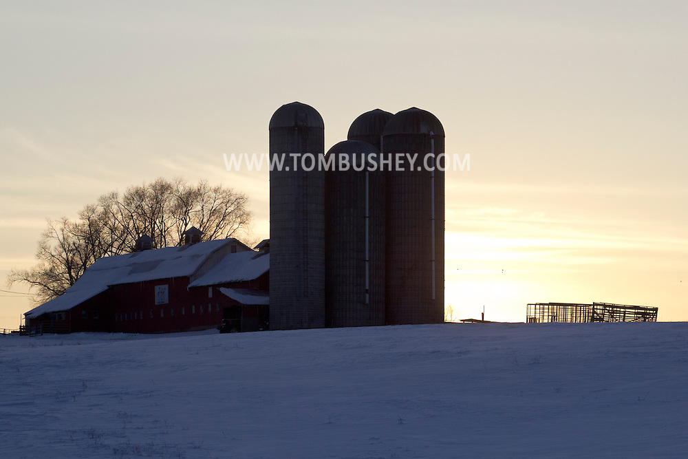 Goshen, New York - The sun sets behind a barn and silos on a farm Feb. 10, 2013.