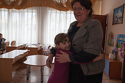 Victoria Mochalova Alexandrovna, the director of Lugansk Orphanage No.1 is hugged by one of the children in her care.
