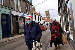 North Berwick, Scotland, UK. 17 December 2020. Scottish Government states that East Lothian is to move from level 2 to level 3 lockdown from Friday 18 December. This means restaurants and bars are not allowed to sell alcohol. Pic;  Members of the public wearing facemasks on High Street in North Berwick.  Iain Masterton/Alamy Live News