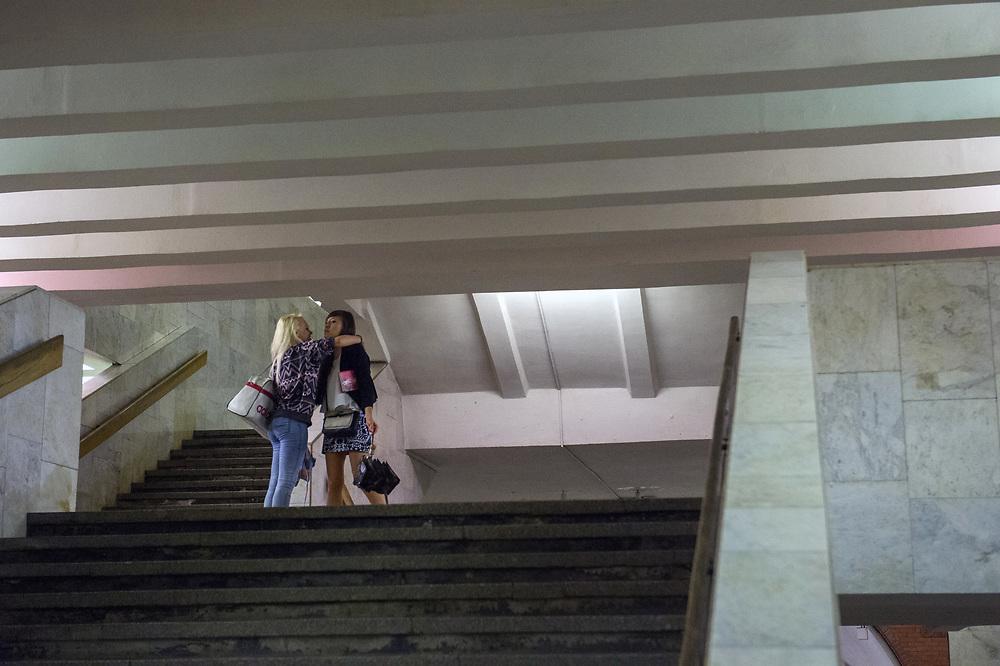 Friends hug goodbye at Biblioteca Im Lenina (The Lenin Library) Metro Station , opened in 1935.