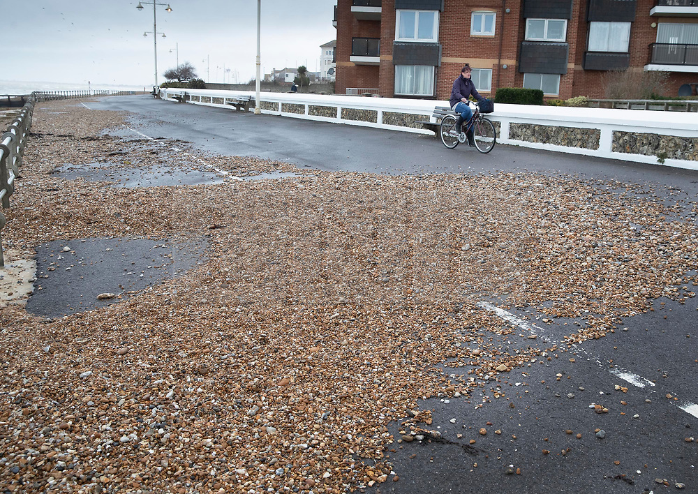 © Licensed to London News Pictures. 08/02/2019. Bognor Regis, UK. A cyclist passes shingle washed up on to the sea front path at Bognor Regis as the effects of Storm Erik are felt in the south of the UK. Photo credit: Peter Macdiarmid/LNP