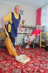 Elderly carer assisting client by hoovering front room,