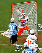 Johns Hopkins (10) shoots past Virginia Cavaliers goalie (18) during the game in Charlottesville, VA. Johns Hopkins defeated Virginia 11-10 in overtime. Photo/Andrew Shurtleff