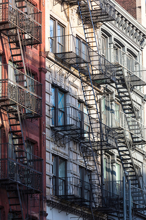 Fire Escape ladders as escape route of tenement blocks of city apartments in Soho area, New York, USA