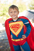 A 4-year-old boy is dressed up in a Superman costume for Halloween.