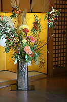 """Ikebana in an Alcove - Ikebana, meaning """"arranged flower"""" is the Japanese art of flower arrangement, also known as kado - the """"way of flowers"""".  More than simply putting flowers in a container, ikebana is a disciplined art form in which nature and humanity are brought together. Contrary to the idea of floral arrangement as a multicolored arrangement of blooms, ikebana emphasizes other areas of the plant, such as its stems and leaves, and draws emphasis towards shape, line and form. Though ikebana is a creative expression it has certain rules governing its form."""