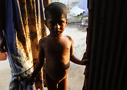 Vithusan Partheepan stands in the doorway after having a bath, Batticaloa, Sri Lanka, July 8, 2005. The Partheepan family, who lost a 4 year old girl named Madusia, first took refuge in the Anapandi Hindu temple after their house was flattened in the tsunami. They were then moved to the Hindu college and placed in tents donated by aid organizations. Six months later, they were still living on the land where their tents were set up, but they also had a partition of their own in a tin hut with a thatched roof. With earned and borrowed money, plus a little given to them for the loss of Madusia, the family bought a small piece of land, where they plan to start anew.