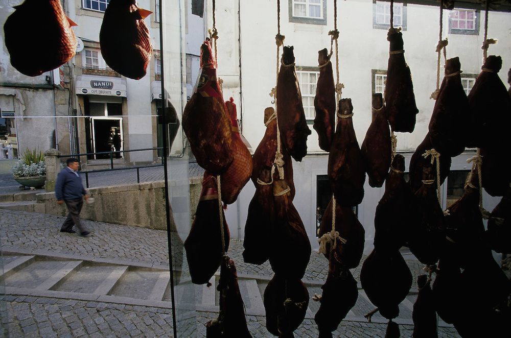 Europe, Portugal, Oporto, Shop window filled with hanging hams