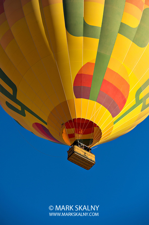Colorful hot air balloon just after lift off.  Set against a deep blue sky.