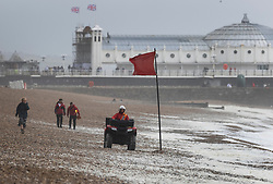 © Licensed to London News Pictures. 30/07/2021. Brighton, UK. A life guard patrols Brighton beach on a quad bike as high wind whips up the waves. Parts of the south are feeling the effects of Storm Evert, the first named storm of summer 2021. Photo credit: Peter Macdiarmid/LNP