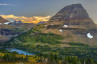 The colors of sunset linger behind Bearhat Mountain in Glacier National Park. The beautiful Hidden Lake wraps around the base of the mountain, before the creek drops to the valley below. Normally there is more snow in this view, but most of it had melted after a hot summer. The distant Gunsight Mountain and Sperry Glacier can be seen on the left.