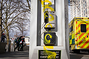 Two NHS (National Health Service) paramedics return from attending a nearby emergency, by a public BT landline phone kiosk which has been vandalised by the spraying of yellow aerosol paint over its handset and keypad on the Southbank in Waterloo, on 11th March 2021, in London, England.