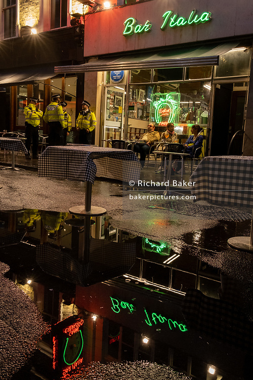 On a rainy night in Soho, tables set up for social distancing remain vacant at a time when recently re-opened bars and restaurants are desperate for customer business during the coronavirus pandemic, on 27th August 2020, in London, England.