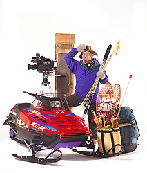 Man with winter clothes,snowmobile,news camera,skis,toboggan,snowshoes,back pack,fur hat