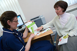 Patient looking at BMI chart with community nurse,