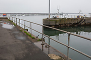 A landscape of dock railings and harbour walls and a seascape of a distant North Sea, on 25th September 2017, in Amble, Northumberland, England.