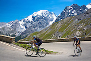 Cyclists ride roadbikes (Guerciotti and Look) uphill on The Stelvio Pass, Passo dello Stelvio, Stilfser Joch, in the Alps, Italy
