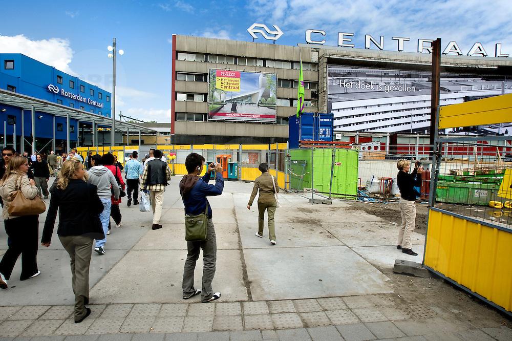"""Nederland Rotterdam 3 september 2007 20070903 ..Voorbijgangers/ reizigers fotograferen en bekijken de vertrouwde oude hal van het voormalige centraal station nog een keer voordat het definitief gesloopt zal worden.  ."""" Het doek is gevallen """" Zondag 2 september is het doek letterlijk doek gevallen voor het in 1957 geopende gebouw. Over enkele weken wordt de schepping van architect Sybold van Ravesteyn gesloopt en komt op het Stationsplein een nieuwe OV-terminal, die na 2011 ruim 300.000 reizigers per dag moet kunnen verwerken. Voorbijgangers maken een foto van het oude bekende centraal station, dat sinds 1957 dienst heeft gedaan. Een gloednieuw station zal op deze plek verrijzen. Op de achetrgrond links het tijdelijke centraal station. ..Het tijdelijke station dat de periode overbrugt tussen de sloop van het oude Rotterdam CS en de bouw van een nieuw station, kost 12 miljoen euro. Dat is een schijntje vergeleken met het half miljard waarop het nieuwe is begroot. De bedoeling is dat de tijdelijke bebouwing in februari klaar is. Het blijft open tot 2010. Het oude gebouw maakt plaats voor vijf tijdelijke. Daarvan zijn er vier voor de reizigers en een voor het personeel van de Spoorwegpolitie. ..Tijdelijk Rotterdam Centraal.1 september 2007..Alle treinreizigers opgelet! Vanaf 2 september sta je voor een dichte deur als je bij Rotterdam Centraal op de trein wilt stappen. Tenzij je de ingang van het tijdelijke Rotterdam Centraal al gevonden hebt. ..Naast het oude vertrouwde station staat al een tijdje een groot blauw gebouw en vanaf 2 september kun je daar op je trein stappen. Je kunt er zelfs een kopje koffie halen, of kleine boodschappen doen. Alle winkels zijn namelijk gewoon verplaatst naar het grootste tijdelijke station van Nederland...Het Centraal Station was al een hele tijd een grote bouwput, want er wordt heel hard gewerkt aan een nieuw, beter en vooral moderner station. Maar omdat afscheid nemen altijd zo moeilijk is, vindt er op 12 september een soort ode aan h"""