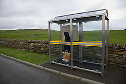 Woman standing at a bus stop in the countryside on Orkney; Scotland,