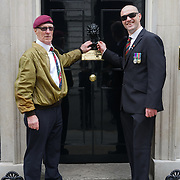 London,England,UK : Chris Taylor and Nigal Kelsall is a founder of UK Veterans - One Voice hang a partition to 10 Downing Street, London. Photo by See Li