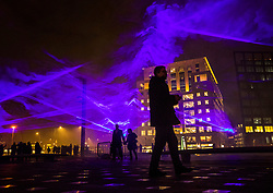 © Licensed to London News Pictures. 17/01/2018. London, UK. Visitors walk through a laser and smoke light show entitled 'Waterlicht' by Daan Roosegaarde as it fills the night sky above Granary Square in King's Cross during the Lumiere London festival. Running from 18th-21st January 2018 more than 50 artworks are transforming the capital's streets, buildings and public spaces into an immersive nocturnal art exhibition of light and sound. Locations include King's Cross, Fitzrovia, Mayfair, West End, Trafalgar Square, Westminster, Victoria, South Bank and Waterloo. Photo credit: Peter Macdiarmid/LNP