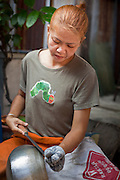 "Mar. 21, 2009 -- BANGKOK, THAILAND:    A woman handcrafts a monk's bowl on Soi Baan Bat. The bowls are made from eight separate pieces of metal said to represent the Buddha's Eightfold Path. The Monk's Bowl Village on Soi Ban Baat in Bangkok is the only surviving one of what were originally three artisan's communities established by Thai King Rama I for the purpose of handcrafting ""baat"" the ceremonial bowls used by monks as they collect their morning alms. Most monks now use cheaper factory made bowls and the old tradition is dying out. Only six or seven families on Soi Ban Baat still make the bowls by hand. Most of the bowls are now sold to tourists who find their way to hidden alleys in old Bangkok. The small family workshops are only a part of the ""Monk's Bowl Village."" It is also a thriving residential community of narrow alleyways and sidewalks.     Photo by Jack Kurtz"