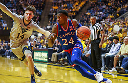 Jan 19, 2019; Morgantown, WV, USA; Kansas Jayhawks guard Lagerald Vick (24) drives baseline past West Virginia Mountaineers guard Chase Harler (14) during the first half at WVU Coliseum. Mandatory Credit: Ben Queen-USA TODAY Sports
