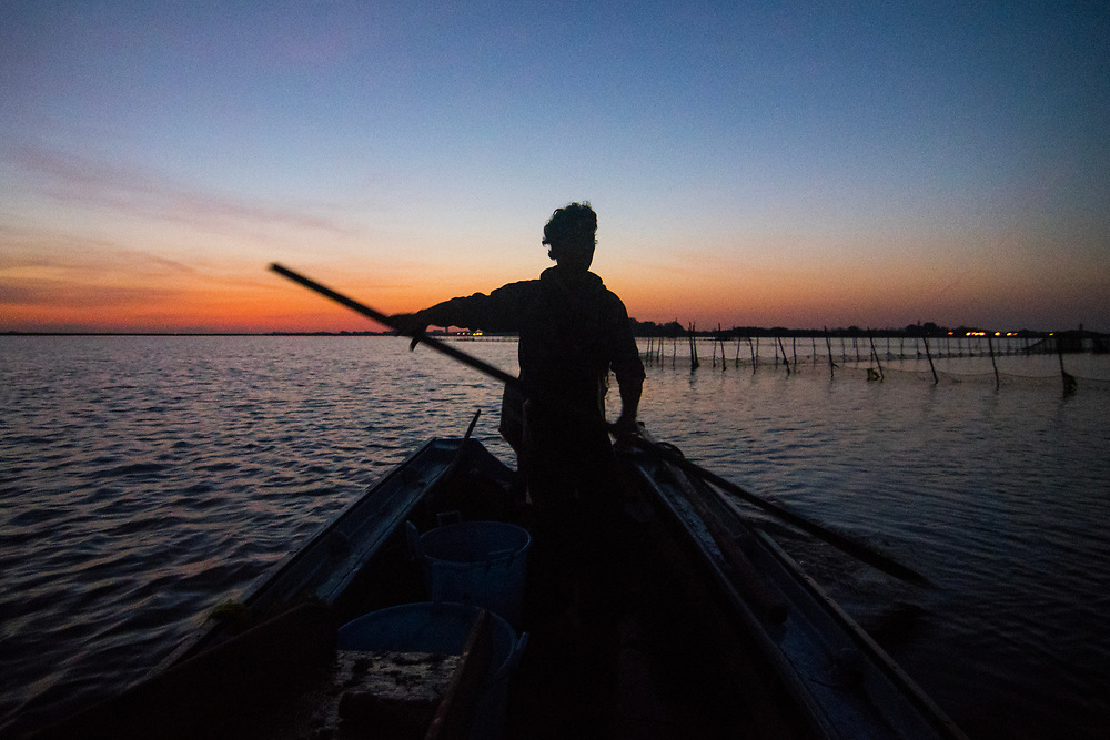 VENICE, ITALY - APRIL 2018. <br /> Emiliano, a moecante (crabs fisherman) of the island of Burano, makes the checking tour of the fishing nets out in the Venetian lagoon during sunrise. He uses a wooden stick to move the boat close to the fishing net, without using the motor of the boat.