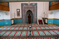 © Licensed to London News Pictures. 15/05/2020. London, UK. Imam Ajmal Masroor performs a Friday prayer service during Ramadan to an empty hall and is broadcasting virtually using his phone, at Wightman Road Mosque in North London during the coronavirus lockdown. Mosques, churches, temples and other places of worship have been closed since 23 March due to the coronavirus lockdown. Photo credit: Dinendra Haria/LNP