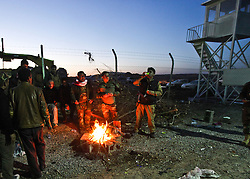 December 4, 2016 - Mosul, Iraq - Peshmerga troops gather around a fire as the sunsets while keeping watch on Internally Displaced People fleeing ISIS from Mosul as Iraqi Security Forces move to clear the city of the terror network adjust to life at Hassan Sham Camp 3 in Kurdistan Region. (Credit Image: © ZUMA Wire via ZUMA Wire)