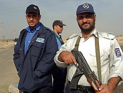 Two  members of the Iraqi police force pose for photos outside a vehicle checkpoint on one of the roads in the Basra area of Iraq.