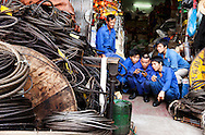 A group of shipyard workers are glued to their friend's video game at a supply store in Hai Phong. Robert Dodge, a Washington DC photographer and writer, has been working on his Vietnam 40 Years Later project since 2005. The project has taken him throughout Vietnam, including Hanoi, Ho Chi Minh City (Saigon), Nha Trang, Mue Nie, Phan Thiet, the Mekong, Sapa, Ninh Binh and the Perfume Pagoda. His images capture scenes and people from women in conical hats planting rice along the Red River in the north to men and women working in the floating markets on the Mekong River and its tributaries. Robert's project also captures the traditions of ancient Asia in the rural markets, Buddhist Monasteries and the celebrations around Tet, the Lunar New Year. Also to be found are images of the emerging modern Vietnam, such as young people eating and drinking and embracing the fashions and music of the West. His book. Vietnam 40 Years Later, was published March 2014 by Damiani Editore of Italy.