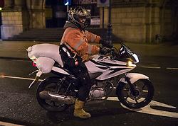 CAPTION CORRECTION © Licensed to London News Pictures. 13/01/2017. Great Yarmouth, UK. A resident carries sandbags on a motorbike to his house near the seafront in Great Yarmouth. The Environment Agency has warned residents to prepare for evacuation as as they fear flooding at tonight's high tide. Photo credit: Peter Macdiarmid/LNP