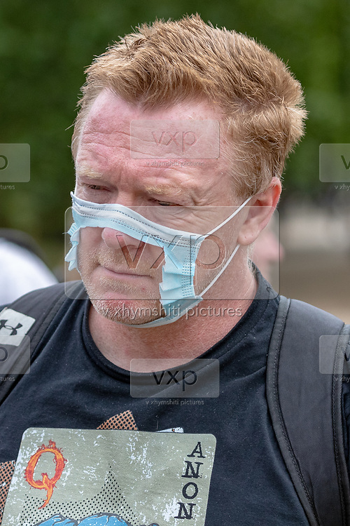 A man wearing a torn mask attends a protest against the wearing of masks during the coronavirus outbreak, near Marble Arch in Central London on Sunday, July 19, 2020. (VXP Photo/ Vudi Xhymshiti)