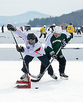 """Scott Harris of Tavern 27 and Paul Frazer of Crosspoint take to the ice for first round """"Just for Fun""""  action during the New England Pond Hockey Classic at Meredith Bay Friday morning.  (Karen Bobotas/for the Laconia Daily Sun)"""