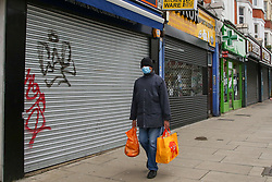 © Licensed to London News Pictures. 15/01/2021. London, UK. A man wearing a protective face covering walks past graffiti written on the shutter of a shop in north London during Coivd-19 lockdown. Supreme court has ruled on a test case by The Financial Conduct Authority (FCA) that hundreds of thousands of small businesses that were forced to close during the first national Covid-19 lockdown will receive insurance payouts on their insurance claims. Photo credit: Dinendra Haria/LNP