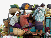 Three women cling on to the sides of a truck loaded with their vegetables and flowers in bamboo baskets for selling at the local market in Bagan, Central Myanmar, Myanmar (Burma).